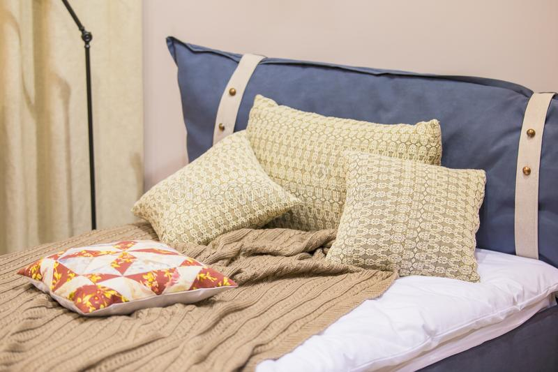 Ett modernt rum för en tonåring i den skandinaviska stilen - en säng, kuddar i stack fall, golvlampan, grov bomullstvillstoppning arkivfoto
