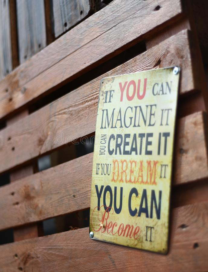 Ett motivational tecken som hänger på en träladugård fotografering för bildbyråer
