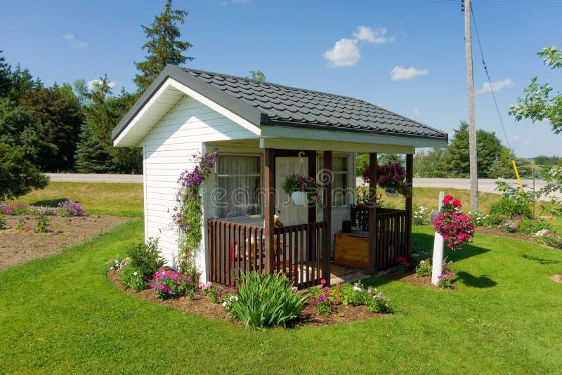 Ett mycket litet hus som omges av blommor royaltyfri fotografi