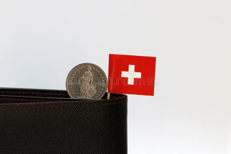 Ett mynt av en schweizisk franc och mini- Schweiz flaggapinne på den svarta plånboken med vit bakgrund Franc Schweiz pengar royaltyfria bilder