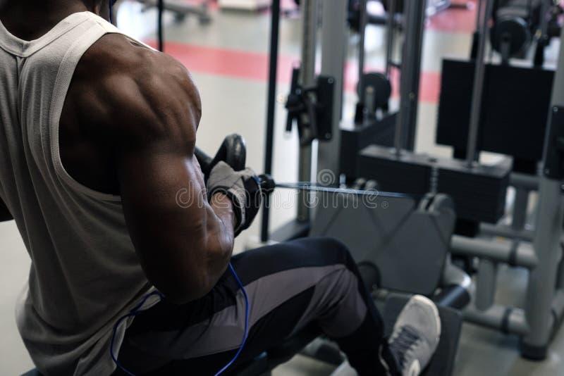Ett nära foto från baksidan av en svart muskulös man i en vit T-tröja som är förlovad i en simulator fotografering för bildbyråer