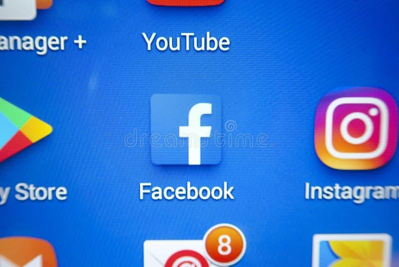 Ett närbildfoto av skärmen för Apple iPhonestart med symbolen för 'Facebook`-apps arkivfoton