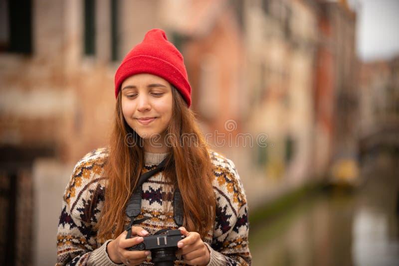Ett nätt anseende för ung kvinna på italienska gator som rymmer en kamera royaltyfri foto