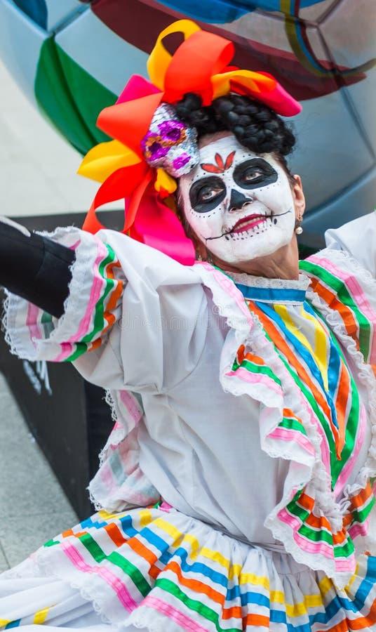 Ett nationellt hus för mexikan fläktar i Gostiny Dvor Beröm av dagen av dödaen Kvinnan klädde som gudinnan av dödperfoen fotografering för bildbyråer