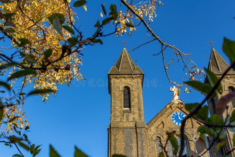 Ett Neo normandiskt kyrkligt torn på blå himmel arkivfoton