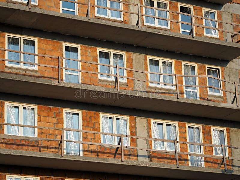 Ett nybyggt kvarter för röd tegelsten med plast- fönster som täckas med folie, konkreta balkonger för grå färger och trätillfälli arkivfoto