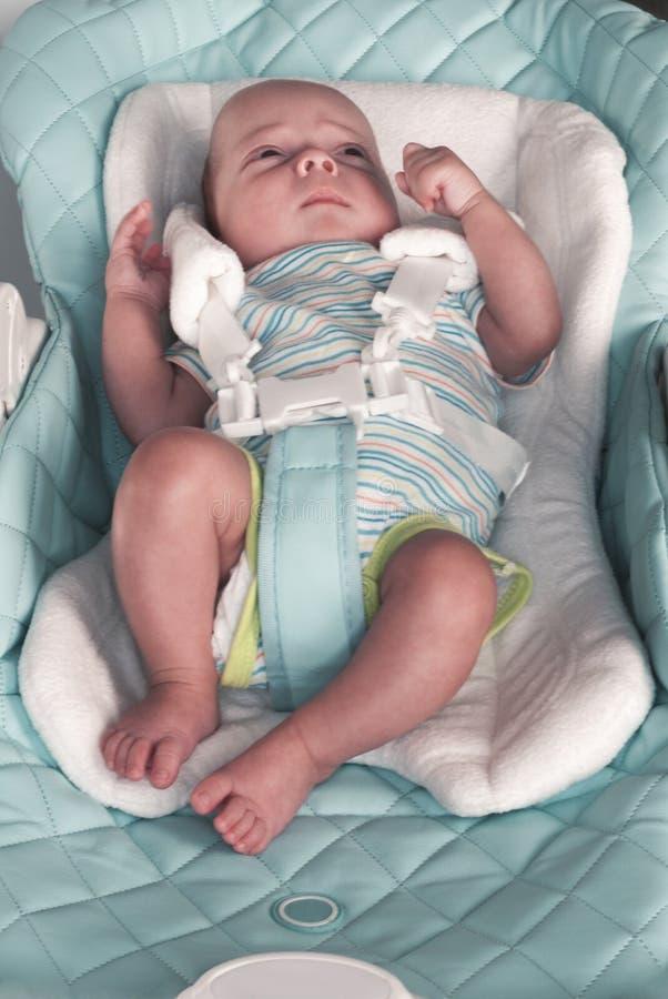 Ett nyfött behandla som ett barn fästs i en highchair för matning med enpunkt sele Selektivt fokusera royaltyfri foto