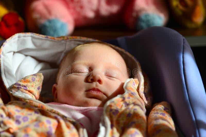 Ett nyfött behandla som ett barn lögner och sömnar i en sittvagn mot bakgrunden av barns mjuka leksaker arkivfoton