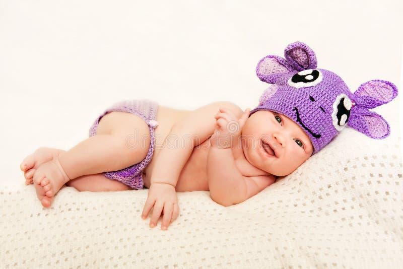 Ett nyfött behandla som ett barn i purpurfärgad luva arkivbild