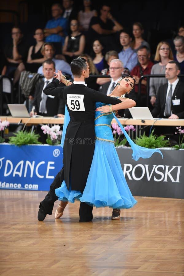 Ett oidentifierat danspar i en dans poserar under normal för storslagen Slam på den öppna mästerskapet för tysk arkivfoto