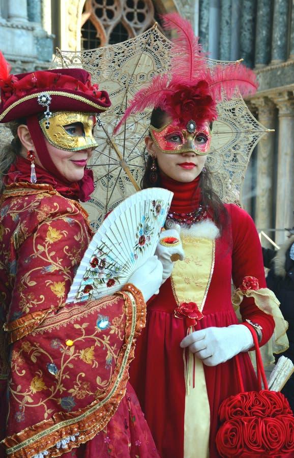 Ett oidentifierat par av kvinnor klär utarbetade röda maskeradkläder med maskeringar, vita handskar, juvlar och hattar med den rö arkivfoton