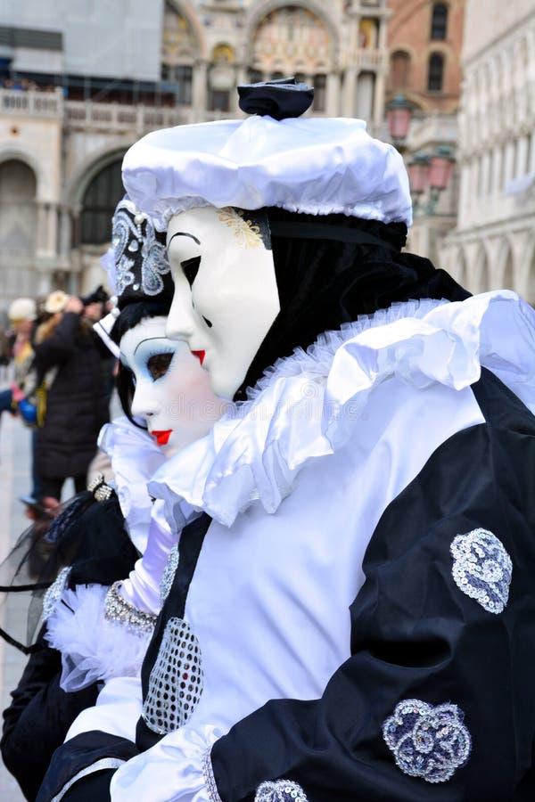 Ett oidentifierat par av maskeradkläder för man- och kvinnakläderpierrot med den svartvita basker under den Venedig karnevalet royaltyfri foto