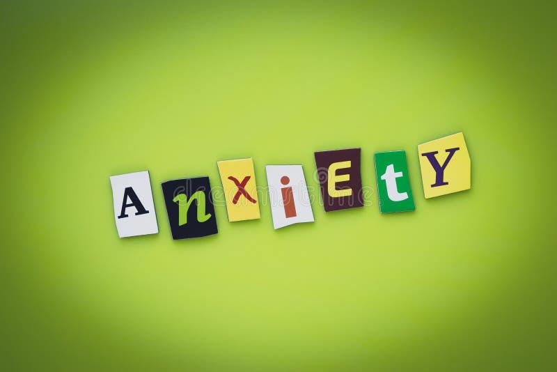 Ett ord som skriver textångest från klippta bokstäver på en grön bakgrund Rubrik - ångest, kort av psykologi Baner med inscriptio arkivfoton