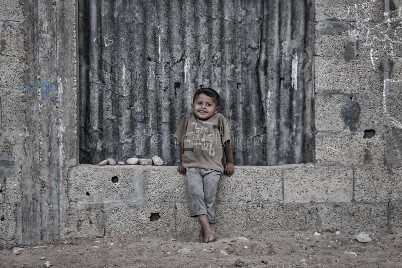 Ett palestinskt barn ler från de döda grannskaparna av den Gaza staden royaltyfria bilder
