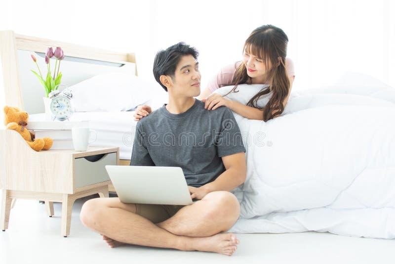 Ett par använder bärbara datorn i deras sovrum royaltyfria bilder