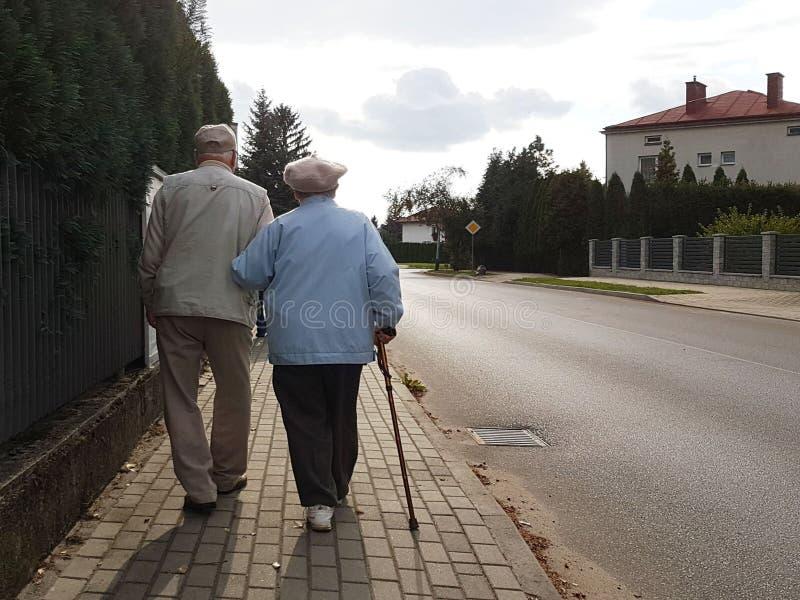 Ett par av äldre folk promenerar trottoaren längs vägen som rymmer händer Farfadern och farmodern på går i a royaltyfri foto