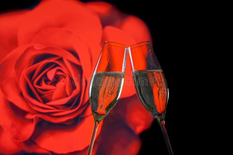 Ett par av champagneflöjter med guld- bubblor på röd rosbakgrund för suddighet arkivfoton