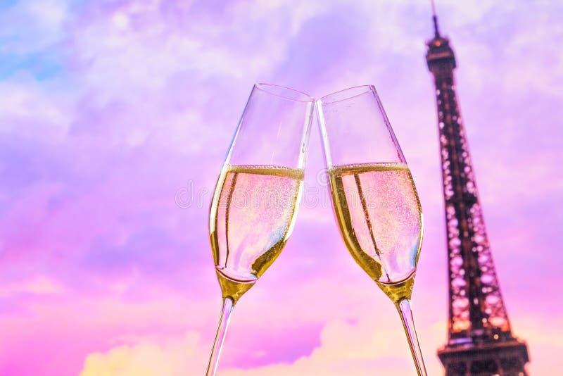 Ett par av champagneflöjter med guld- bubblor på solnedgångsuddighet står högt Eiffel bakgrund royaltyfri bild