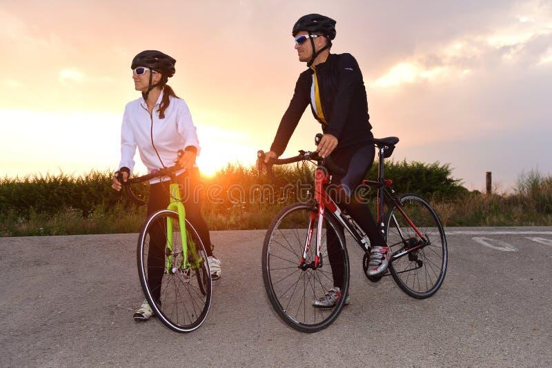 Ett par av cyklister som stoppas på vägen royaltyfri bild