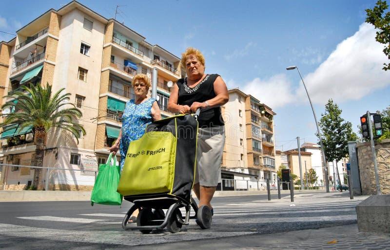 Ett par av damer går tillbaka från marknaden med bilen mycket av livsmedel arkivfoto