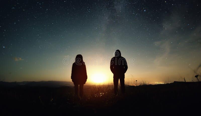 Ett par av den folkmannen och kvinnan står på solnedgången av månen under den stjärnklara himlen med ljusa stjärnor och en mjölka royaltyfria foton