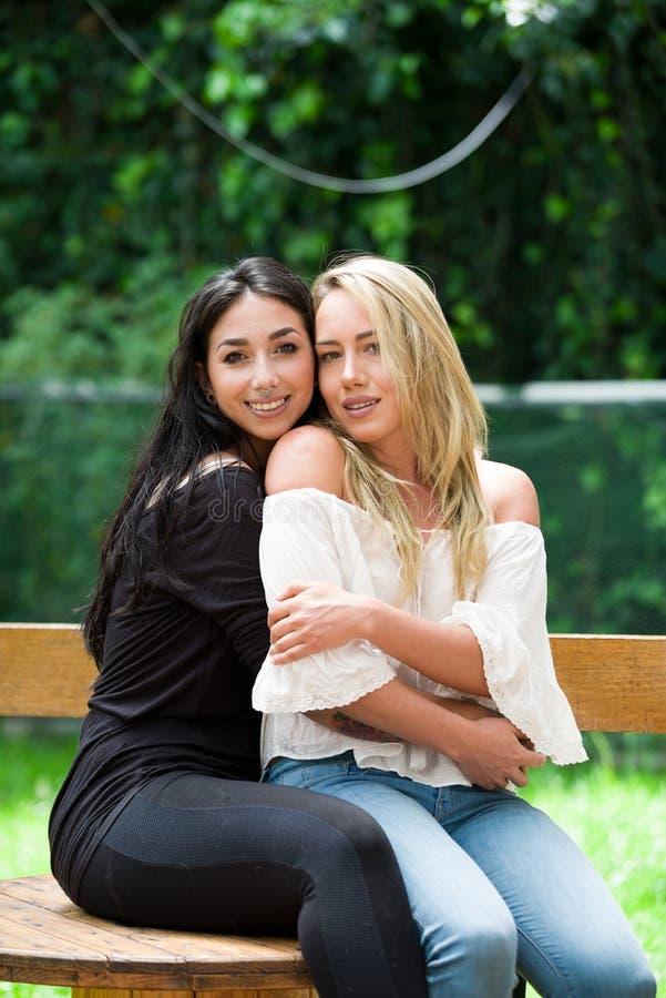 Ett par av den stolta lesbiska kvinnan i det fria som sitter på en trätabell, brunettkvinna, kramar en blond kvinna, i en trädgår arkivfoton
