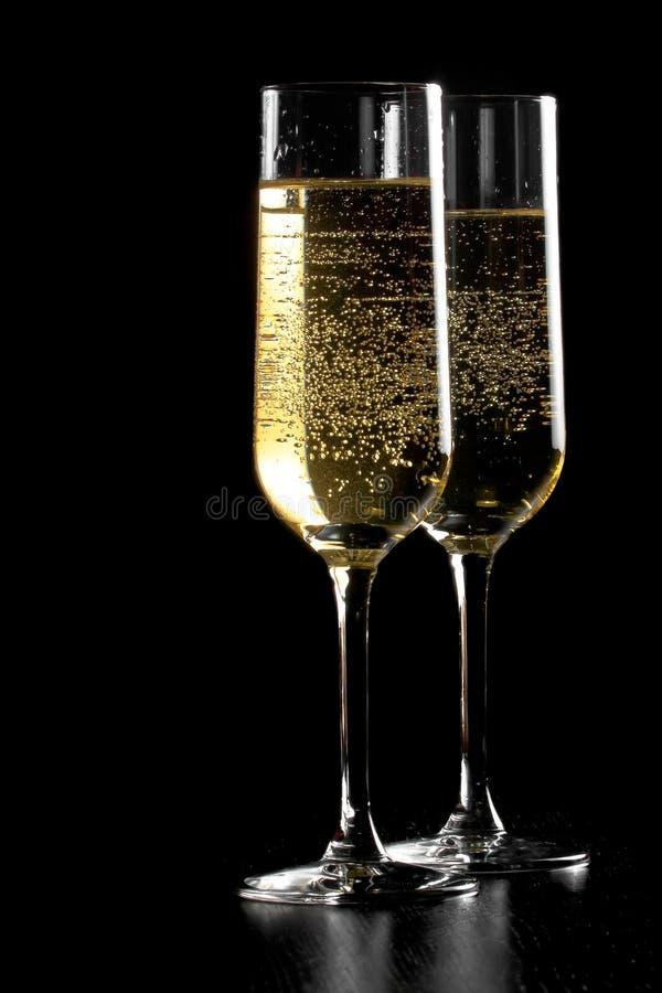 Ett par av flöjter av champagne med guld- bubblor på svart wood bakgrund royaltyfria foton