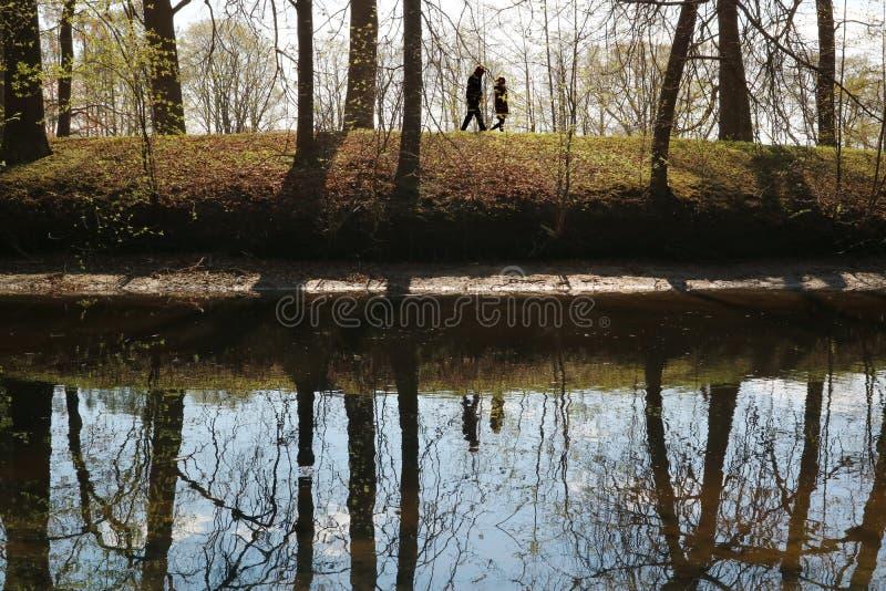 Ett par av folk som promenerar flodbanken i skognaturen royaltyfria foton