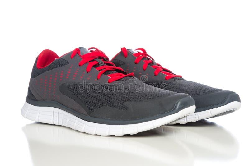 Ett par av gråa rinnande skor med röda skosnöre på en vit backg arkivfoto