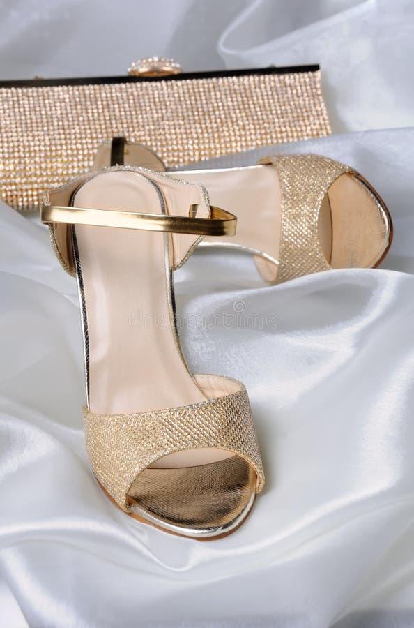 Ett par av guld- sandaler arkivbilder