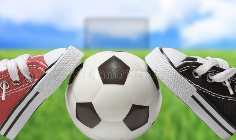 Ett par av gymnastikskor av olika färger lutar på en fotbollboll på bakgrunden av ett fotbollfält och en blå himmel royaltyfria foton