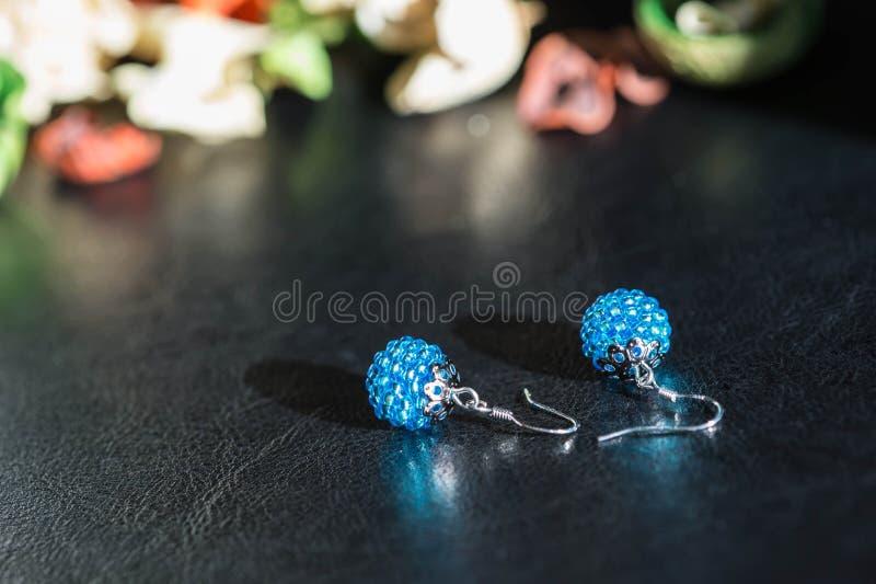 Ett par av handgjorda örhängen från pärlor av turkos färgar arkivbilder