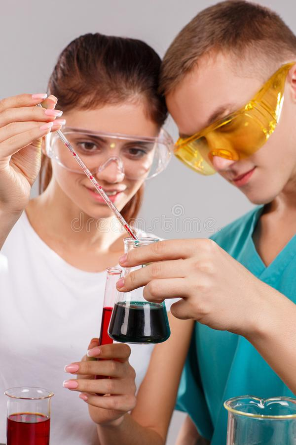 Ett par av kemister tillfogar en röd flytande till en flaska med en grön flytande Begreppet av vetenskap Närbild arkivfoton
