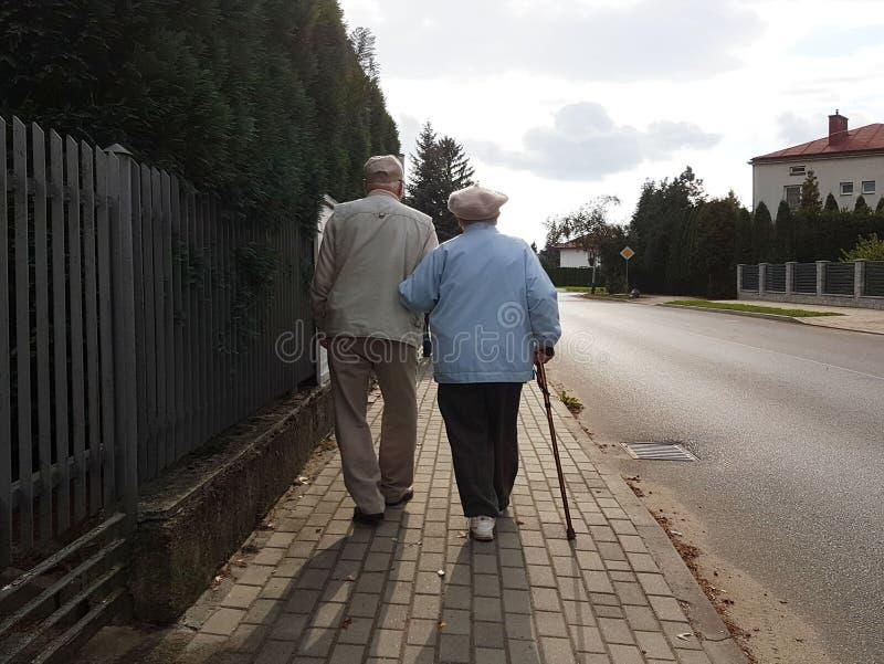 Ett par av ?ldre folk promenerar trottoaren l?ngs v?gen som rymmer h?nder Farfadern och farmodern p? g?r i a fotografering för bildbyråer