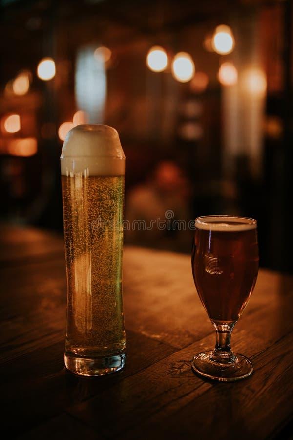 Ett par av olika öl på en trätabell royaltyfria bilder