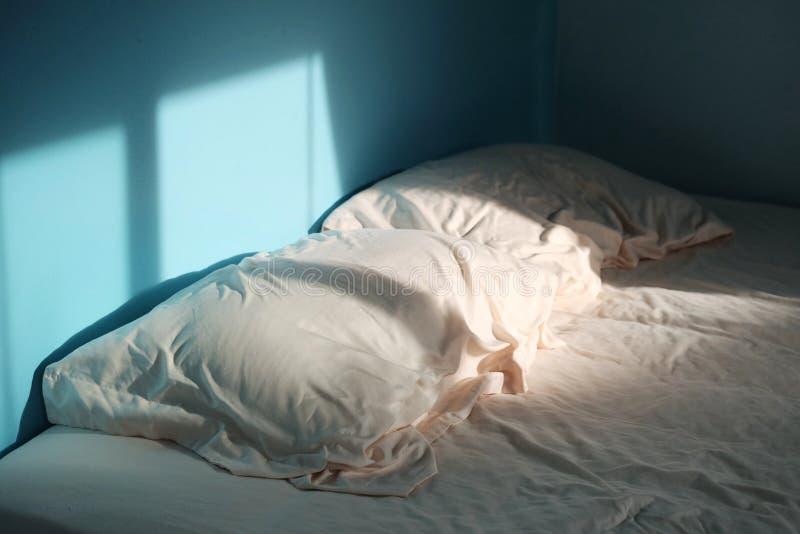 Ett par av rynkiga kuddar med en bedsheet i det blåa rum- och morgonljuset royaltyfri bild