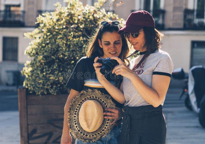 Ett par av sighten för glad kvinna tillsammans som ler och ser hans reflexfotokamera Samma könsbestämmer unga gifta kvinnliga par arkivfoto