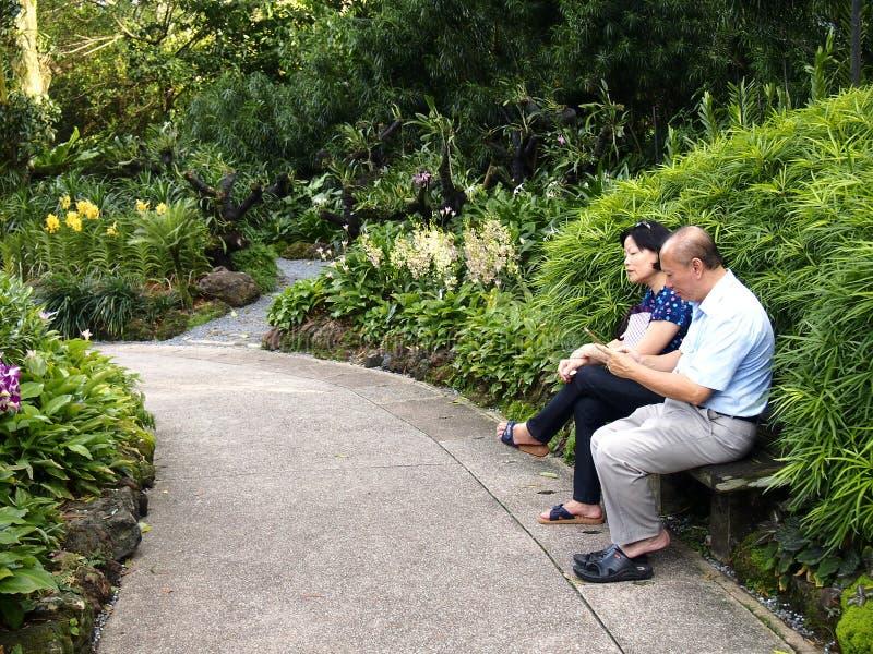 Ett par av turister sitter och vilar på en parkerabänk arkivbild