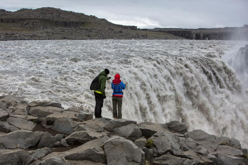 Ett par av turister står på mycket kanten av den kraftiga vattenfallet Dettifos arkivbilder