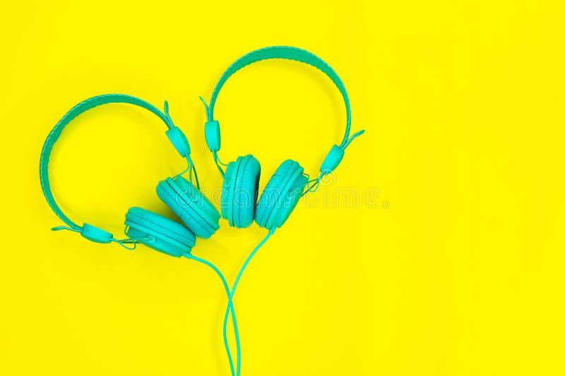 Ett par av turkoshörlurar i formen av en hjärta på en gul bakgrund Begrepp för sommarförälskelsemusik med kopieringsutrymme arkivfoto