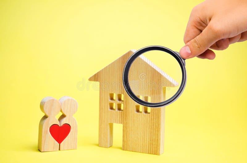 Ett par av v?nner st?r n?ra huset Begreppet av att finna en l?genhet eller ett hus Som man har r?d med hus f?r unga familjer royaltyfri bild