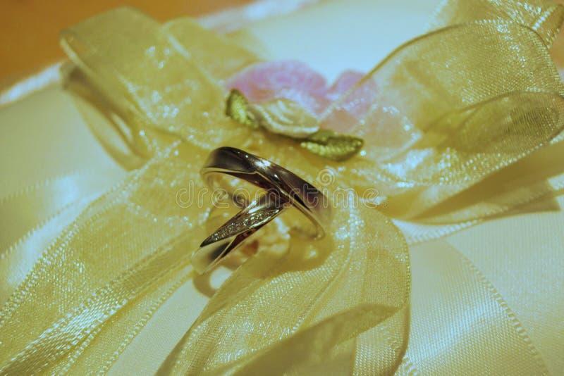 Ett par av vigselringar som vilar på en kudde av det guld- satängbandet och pilbågar royaltyfria bilder
