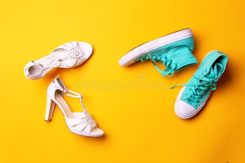 Ett par av vita h?g-heeled sandaler och ett par av turkosgymnastikskor p? gul bakgrund royaltyfri fotografi