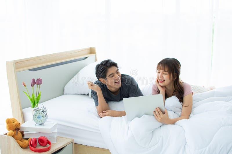 Ett par genom att använda bärbara datorn med lyckligt på sängen royaltyfri bild