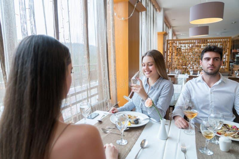 Ett par med en kvinnlig vän som har konversation i en restauran arkivfoton