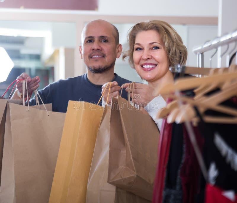 Ett par med shoppingväskor i butiken royaltyfri bild
