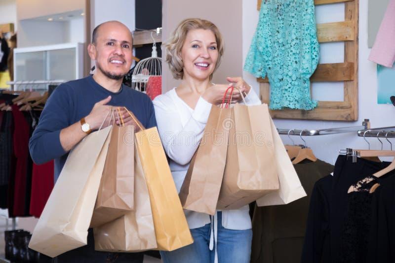 Ett par med shoppingväskor i händerna arkivfoton