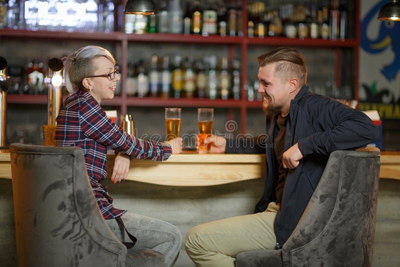 Ett par meddelar sammanträde i en stång som dricker öl och att skratta inomhus royaltyfri foto