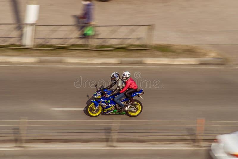 Ett par på en blå motorcykelväg för sport på en stadsväg En man med kvinna som kör motorcykel på gatan med hög hastighet begrepp royaltyfria bilder