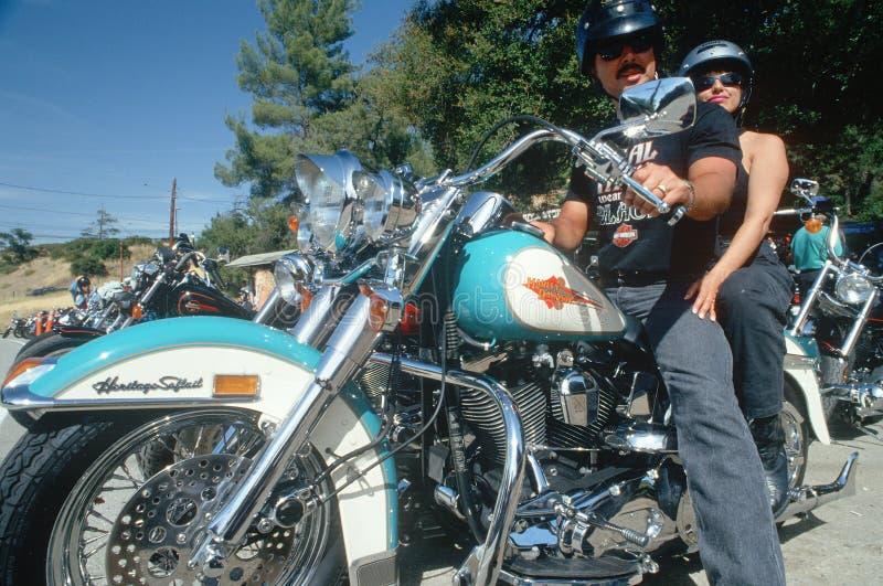 Ett par på en Harley Davidson motorcykel, royaltyfri foto